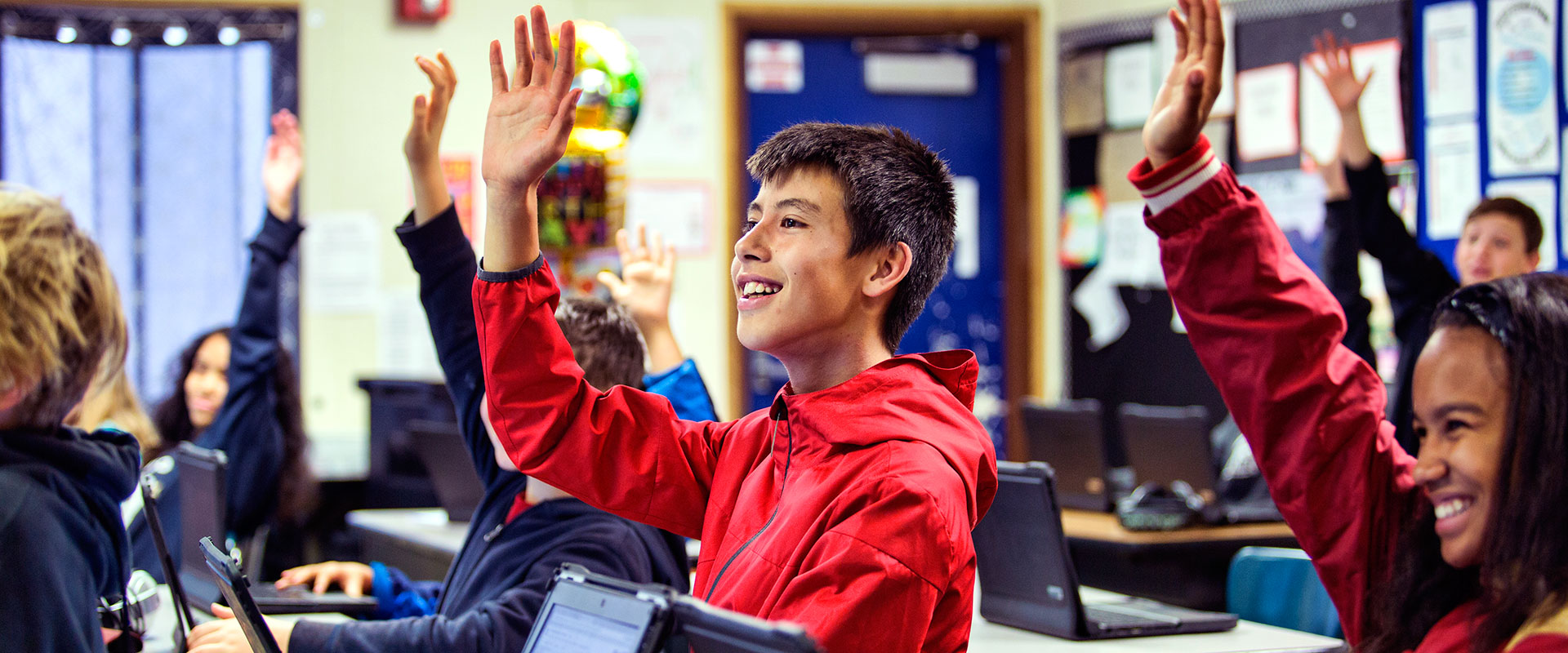 Elementary students in a computer lab raising their hands and smiling